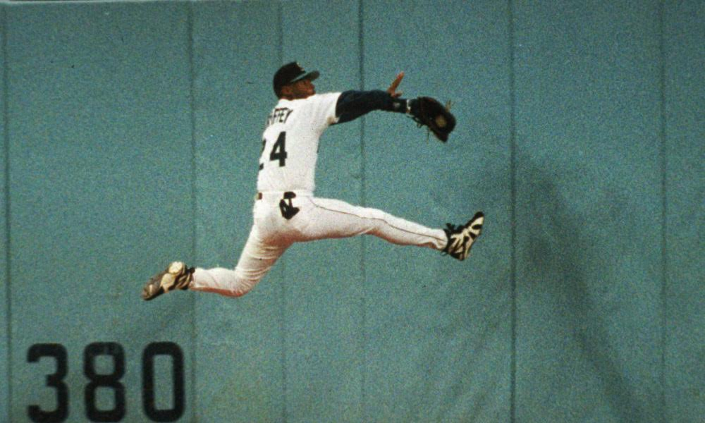 FILE - In this May 26, 199, 5 file photo, Seattle Mariners' Ken Griffey Jr. makes a leaping catch of a ball hit by Kevin Bass of the Baltimore Orioles during a baseball game in Seattle. Ken Griffey Jr. seems assured of election to the Baseball hall of Fame on the first try Wednesday, Jan. 6, 2016, possibly with a record vote of close to 100 percent. Mike Piazza, Jeff Bagwell and Tim Raines also were strong candidates to gain the 75 percent needed for baseball's highest honor. (AP Photo/Gary Stewart, File) ORG XMIT: NY164